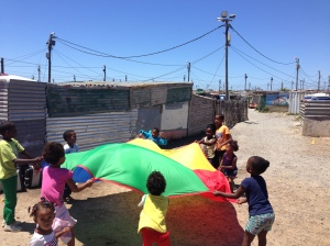 Overcome Heights children playing water balloons parachute